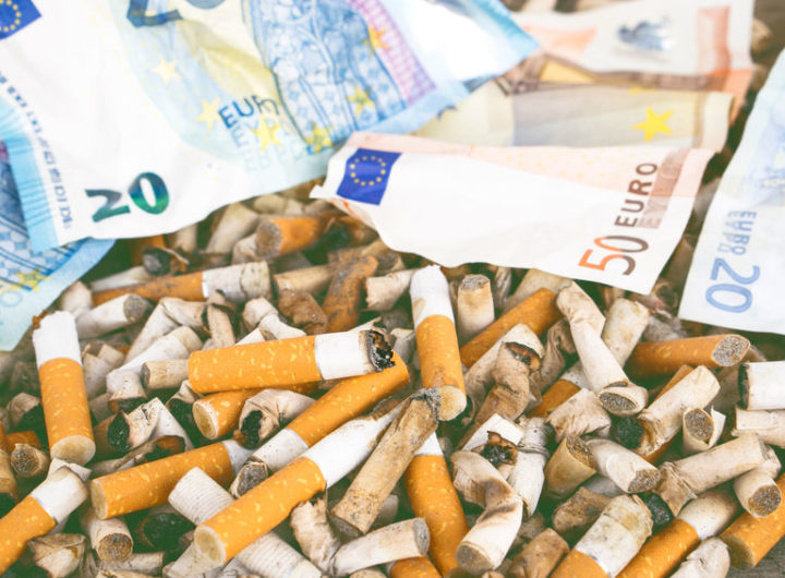 Cigarette butts with euro banknotes background - Concept of waste of health and money lost due to smoking addiction - Lowered black tones with soft vintage filter look